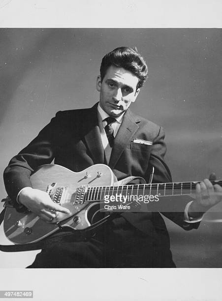 Posed portrait of singer Lonnie Donegan with his guitar January 1959
