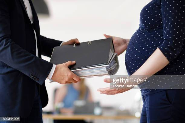 Posed scene A pregnant woman gets file folders in the office from a supervisor on June 21 2017 in Berlin Germany
