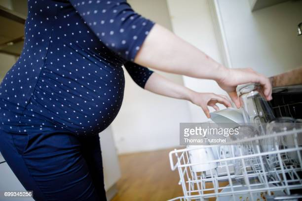 Posed scene A pregnant woman is filling the dishwasher on June 21 2017 in Berlin Germany