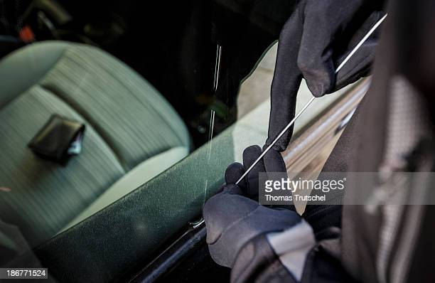 Posed scene of a auto burglary here a closeup of a thief breaking into a car in which a wallet is laying on the front seat on October 22 2013 in...