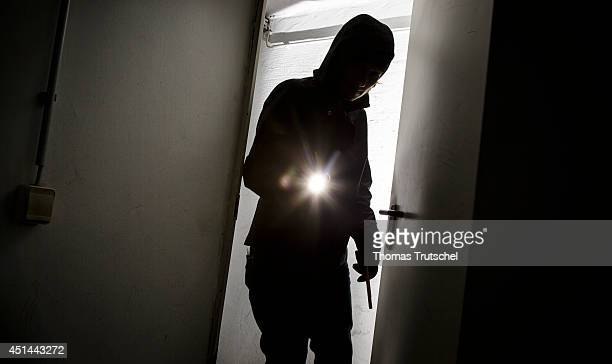 Posed scene of a man with a flashlight standing in an open door on June 27 in Berlin Germany The photo symbolizes the increasing risk of burglary in...