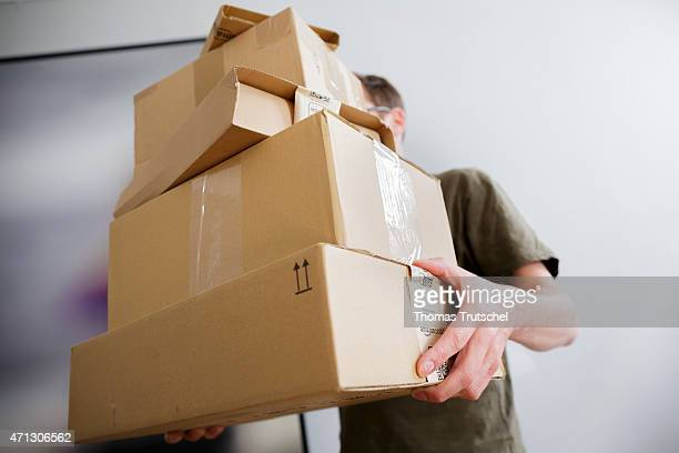 Posed scene on the topic parcel post a man is carrying a stack of packages on April 21 2015 in Berlin Germany Photo by Thomas Trutschel/Photothek via...