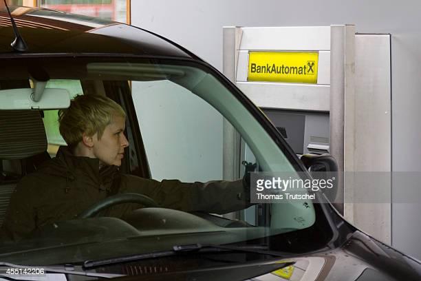 Posed scene young woman withdrawing money at a drivethrough of the Raiffeisenbank on August 24 in Zell am See Austria