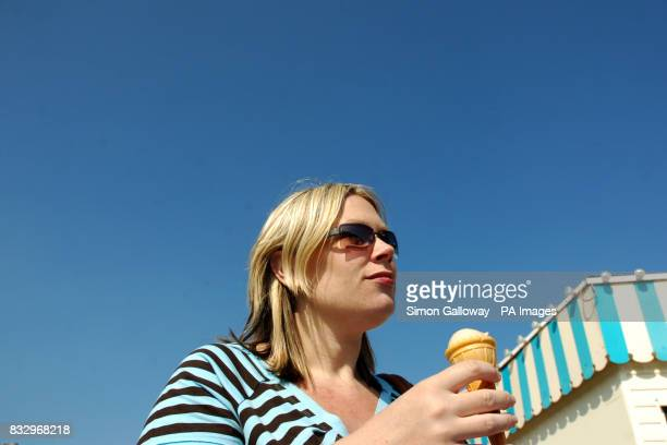 A posed shot of a women eating a ice cream at the seaside