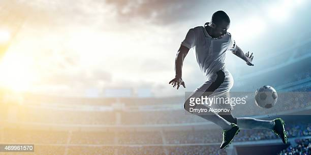 Posed soccer player kicking a ball