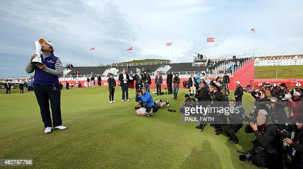 Posing for members of the media South Korea's Park Inbee kisses the trophy as she celebrates her victory after her final round 65 on day four of the...