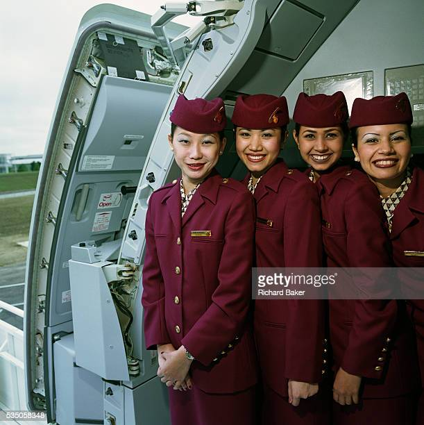Posing in the open doorway of an Airbus A319CJ Business jet four female cabin crew members wear the uniforms of Qatar Airways whose airline has made...