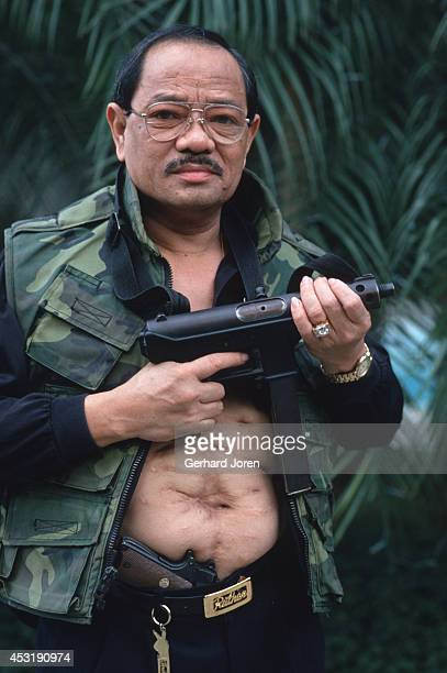 Posing with his Uzi machine gun Ruther Batuigas now a criminal reporter formerly a bounty hunter and owner of Bulls Eye a security company that hires...