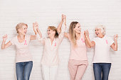 Positive cancer survivors wearing pink, holding each other hands