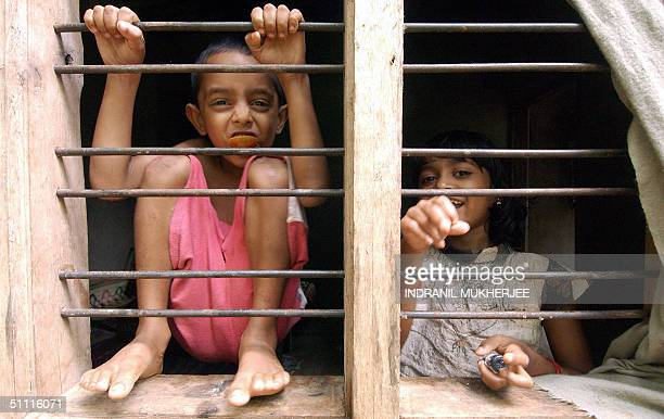 HIV positive children Ananathakrishnan S and Akshara R play at the window of their house 26 July 2004 in the Kottiyoor village of India's southern...