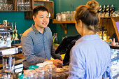 Positive confident cashier taking customers order and asking about preferences. Smiling handsome young staff friendly talking to client. Coffee shop company concept
