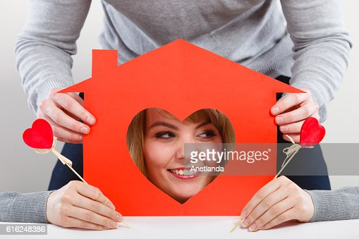 Positive couple with heart house. : Stock Photo