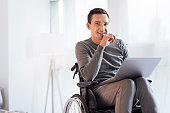 Having secret. Enigmatical male keeping smile on his face and holding glasses in right hand while sitting on the wheelchair