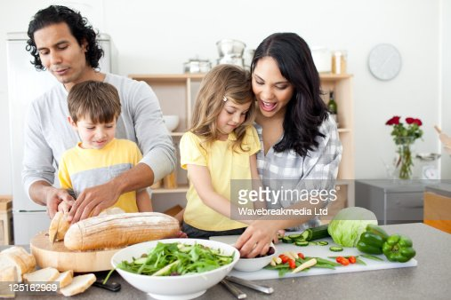 Positive family preparing lunch together : Stock Photo