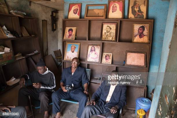 Positive films which were developed and archived in the past and the framed old photo prints are seen as people sit at Daouda Coulibaly's photo...