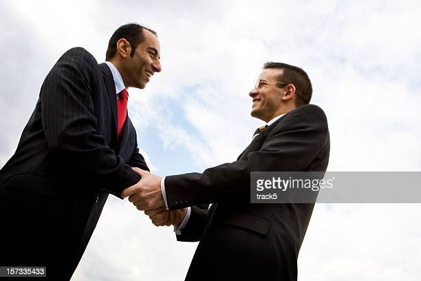Positive handshake and eye contact between diverse business men