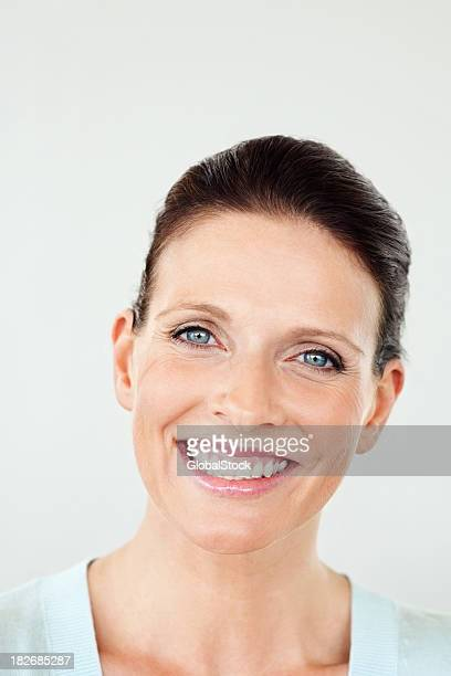Positive middle aged woman giving you a warm smile