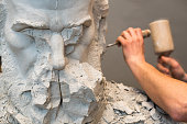Hands of sculptor and hammer detail while carving.