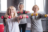 More exercises. Positive persistent nice women standing together and working out with dumbbells while trying to lose some weight