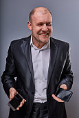 Positive smiling business man talking on two mobile phones very emotional in office suit on grey studio background. Closeup portrait