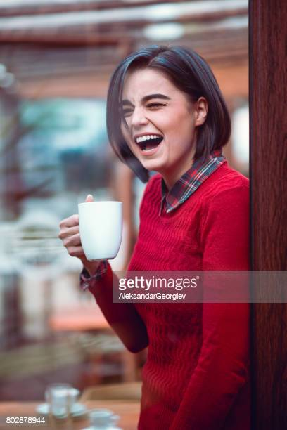 Positive Smiling Female Drinks Coffe and Looking Through Window