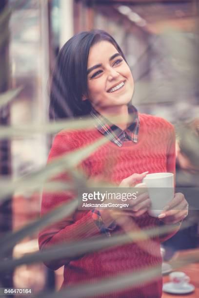 Positive weibliche Getränke Kaffee lächelnd und Blick durch Fenster