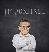 Positive thinking in life attitude concept. Happy confident smart smiling boy standing in front of a black blackboard