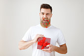 Positive young male has trendy hairdo, long thick beard covered with paper hearts, blinks eye and holds gift box, decorated with red ribbon, flirts with girlfriend, isolated over white background.