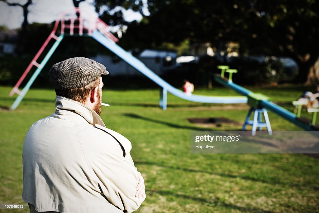 Possible pedophile watches a children's playground for potential prey : Stock Photo