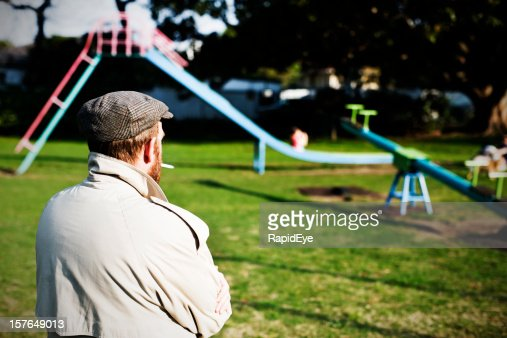 Possible pedophile watches a children's playground for potential prey : Bildbanksbilder
