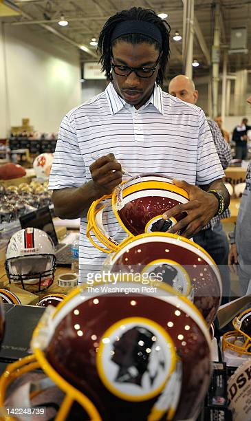 Possible Redskins Draft pick Robert Griffin III signs a group of Redskins helmets He was on hand to sign autographs at a sports memorabilia show at...