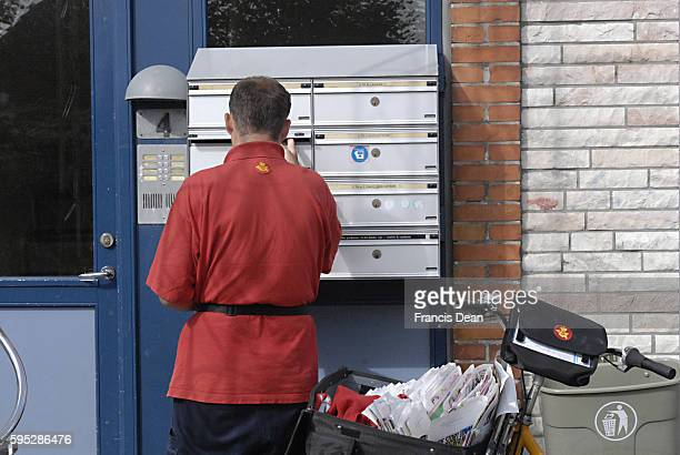 Post Danmark mail man distributing mails to boxes with name of each hold house 26 July 2011