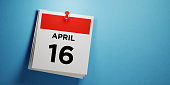 Post it calendar on blue background. April 16 writes on post it note. Panoramic composition with copy space. Emancipation day reminder concept.
