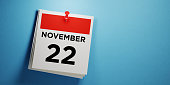 Post it calendar on blue background. November 22 writes on post it note. Panoramic composition with copy space. Thanksgiving reminder concept.