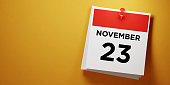 Post it calendar on yellow background. November 23 writes on post it note. Panoramic composition with copy space. Day After Thanksgiving reminder concept.