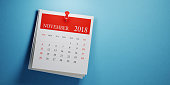 Post it November calendar on blue background. Panoramic composition with copy space. Calendar and reminder concept.