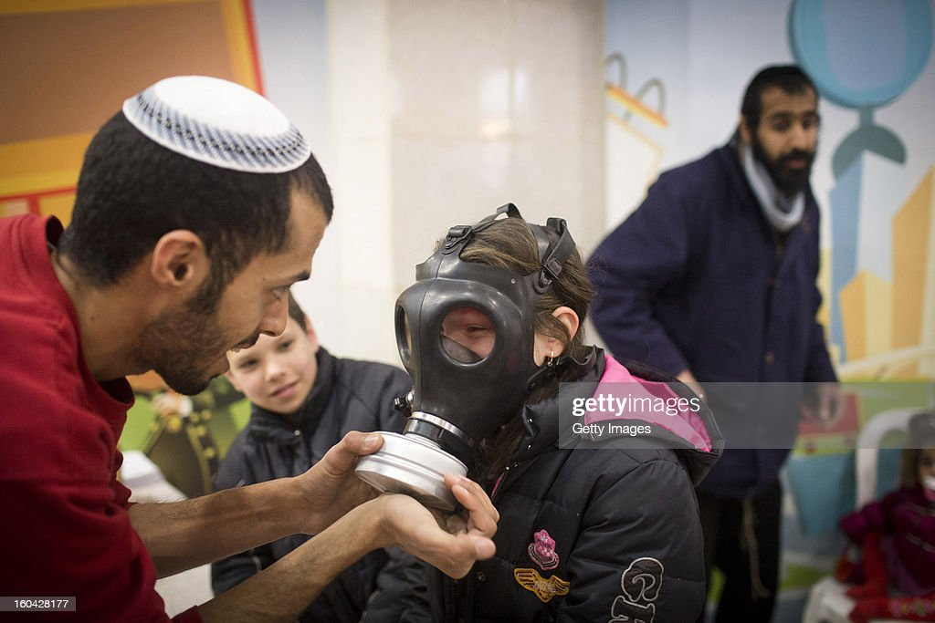 A post office worker shows to an Israeli child how to wear a gas mask at a gas mask kit distribution station in a mall January 31, 2013, in Pisgat Ze'ev, East Jerusalem, Israel. Israel remains on high alert after the Israeli air force reportedly launched an airstrike January 30, on a convoy that Israeli officials said was carrying weapons from Syria to Lebanon on the Syria-Lebanon border.