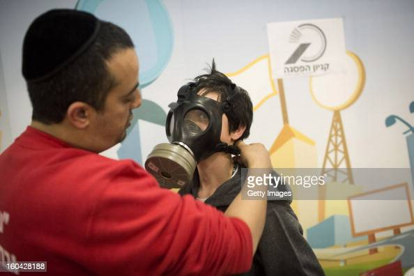 A post office worker shows to an Israeli child how to wear a gas mask at a gas mask kit distribution station in a mall January 31 in Pisgat Ze'ev...