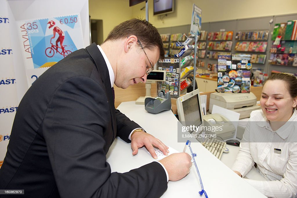 A post worker looks on as Latvian Prime Minister Valdis Dombrovskis (L) signs a letter with the first edition of a Latvia stamp denominated in both lats and euros in Riga on January 30, 2013. Unfazed by the eurozone crisis, Latvia is poised to pass key legislation on January 31, 2013, paving the way for a request for EU approval of its entry as the zone's 18th member on January 1, 2014.