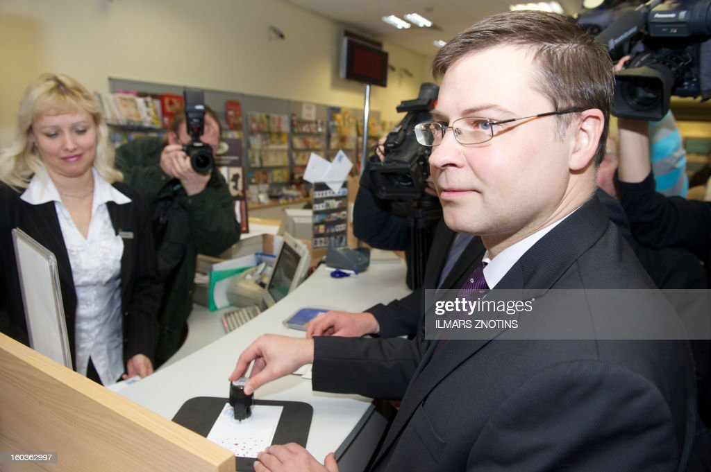 A post worker looks on as Latvian Prime Minister Valdis Dombrovskis (R) validates a letter with the first edition of a Latvia stamp denominated in both lats and euros in Riga on January 30, 2013. Unfazed by the eurozone crisis, Latvia is poised to pass key legislation on January 31, 2013, paving the way for a request for EU approval of its entry as the zone's 18th member on January 1, 2014.
