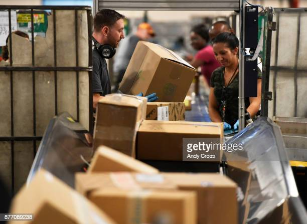 S Postal clerks Stven Prince left and Alyssa Loomis right scan and process packages at the US Postal Denver Processing and Distribution Center...