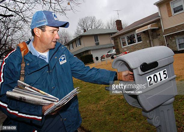 S Postal Service carrier Ron Comly carries parcel packages to a home while delivering mail along his postal route December 17 2003 in Philadelphia...