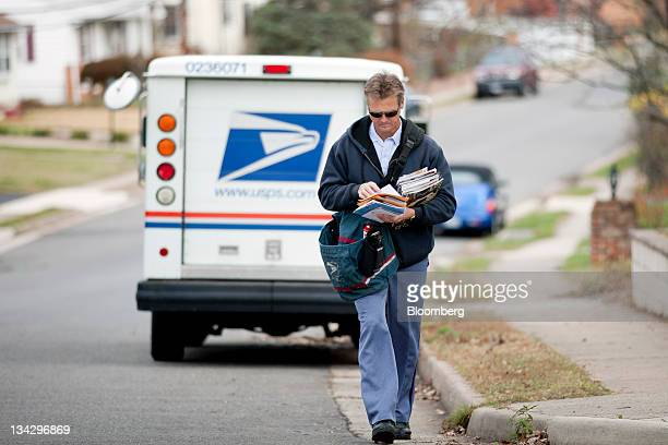 US Postal Service city letter carrier Roy Sipe delivers mail to homes in Fairfax Virginia US on Wednesday Nov 30 2011 The USPS which forecasts a...