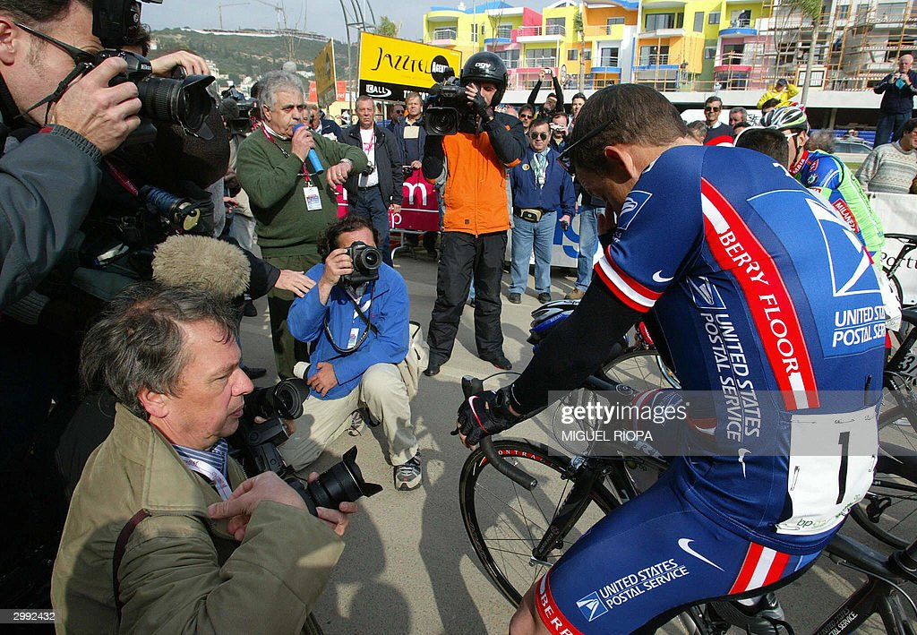 US Postal Service cycling team leader Lance Armstrong (R) bows his head during a minute of silence in memory of Italian cycling star Marco Pantani, before the start of the first stage of the 30th Tour of Algarve, in Albufeira, south Portugal, 18 February 2004. Armstrong said he was stunned and shocked at the news that Pantani had been found dead 14 February 2004 in his hotel room in the chic Italian resort of Rimini. AFP Photo / Miguel RIOPA
