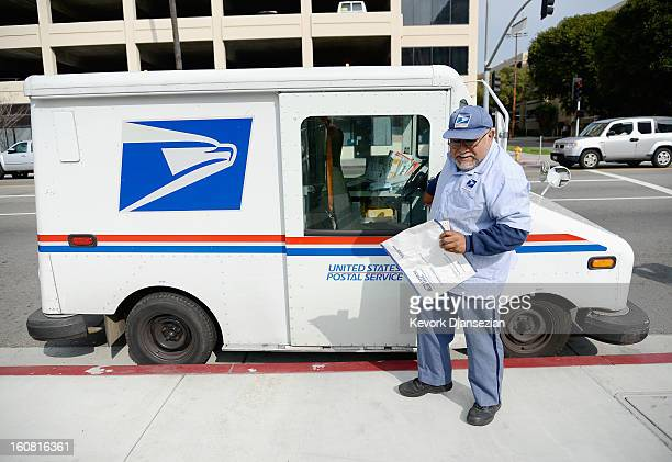 S Postal Service employee Arturo Lugo delivers an Express Mail package during his morning route on February 6 2013 in Los Angeles California The US...
