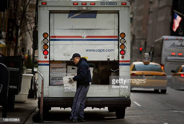 A US Postal Service employee takes mail out of a truck for delivery in New York US on Thursday Nov 15 2012 The US Postal Service said its net loss...