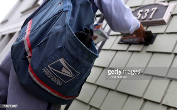 Postal Service letter carrier Anthony Ow places letters in a mailbox as he walks his delivery route July 30 2009 in San Francisco California The US...