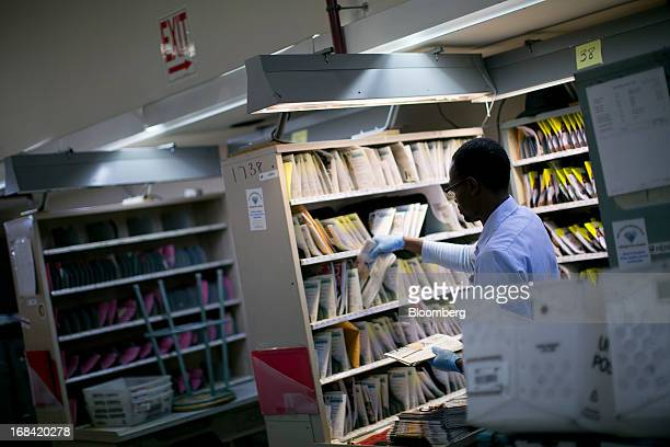 US Postal Service letter carrier James Benjamin prepares mail for delivery at the Brookland Post Office in Washington DC US on Thursday May 9 2013...