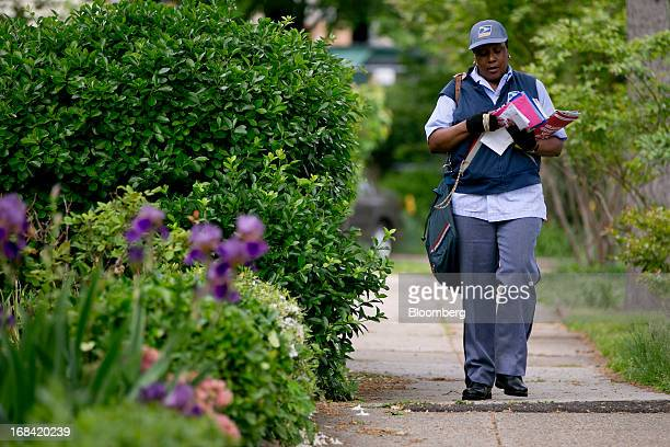 US Postal Service letter carrier Sharon Herbert delivers mail in Washington DC US on Thursday May 9 2013 The USPS is projecting a loss of as much as...