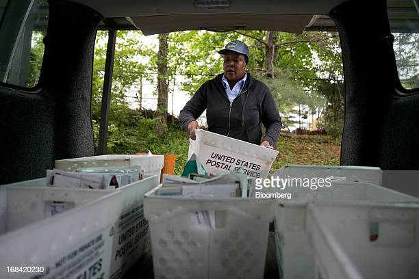 US Postal Service letter carrier Sharon Herbert loads crates of mail into a delivery van at the Brookland Post Office in Washington DC US on Thursday...